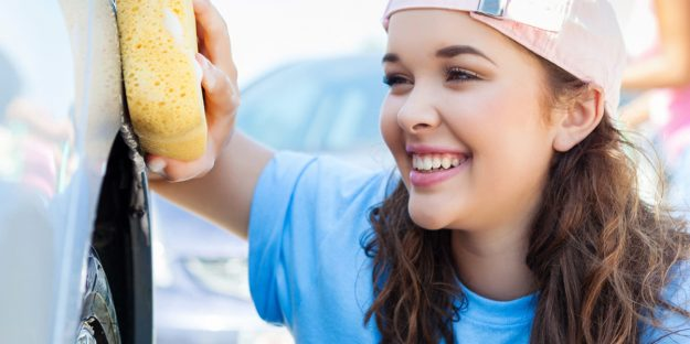 close up of smiling teenager washing car with sponge