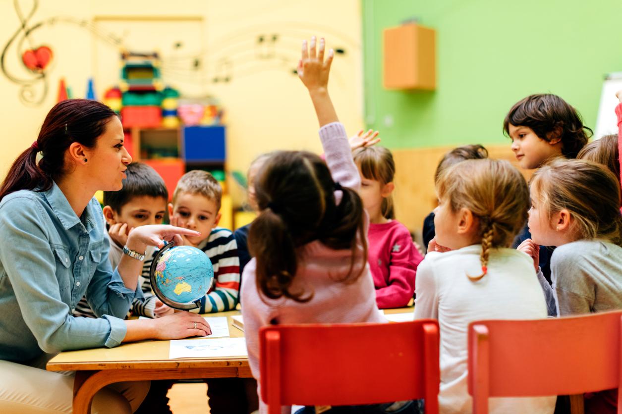 Preschool teacher teaching her children about geography by using globe. Children asking questions.