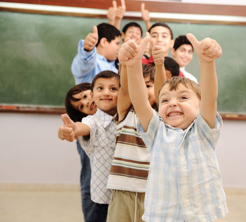 group of younger children with thumbs up gesture. young boy in front with a huge smile.