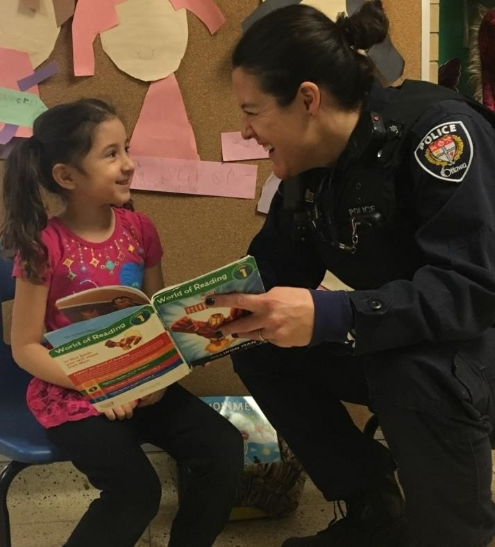 police woman smiling and reading to young girl
