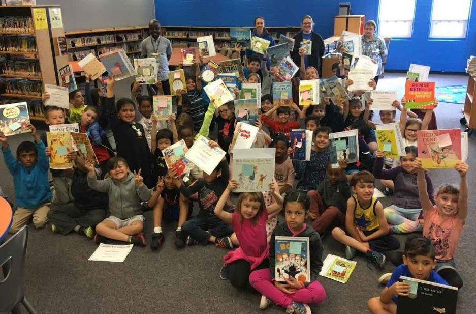 large group of kids holding books