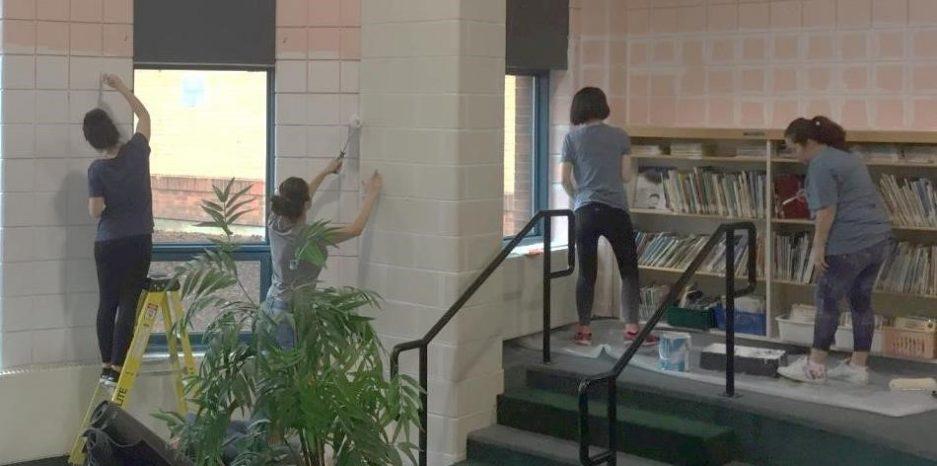 volunteers painting in a school