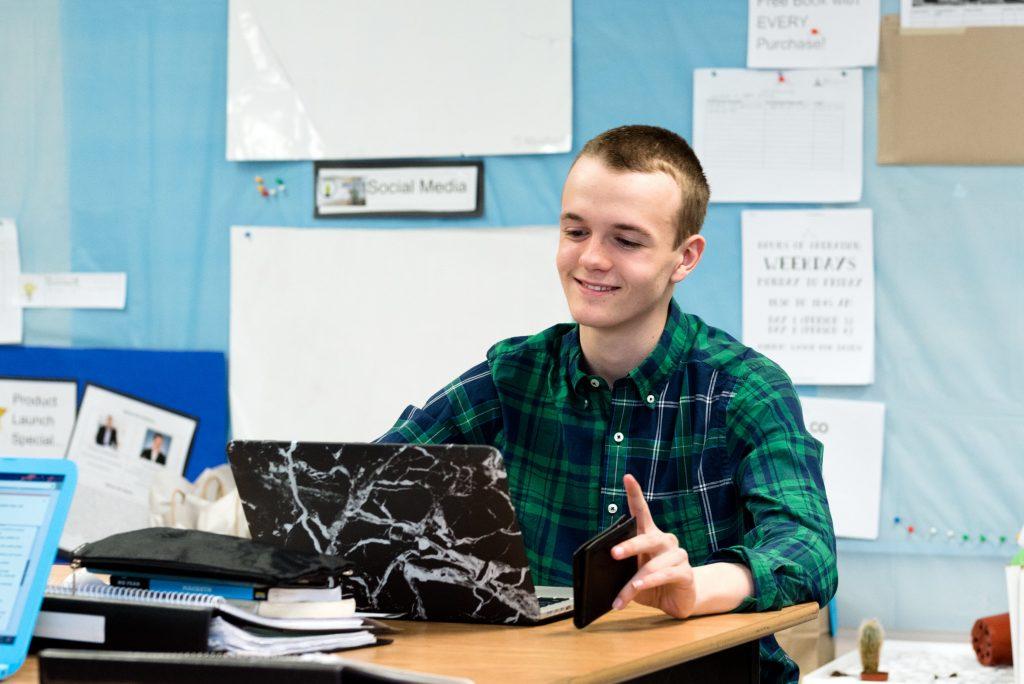 Young man at computer smiling