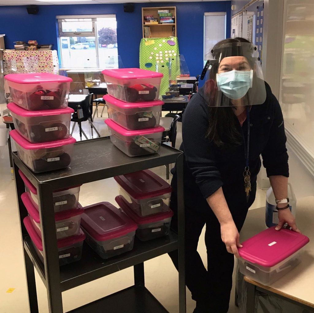 Teacher in mask and visor distributing breakfast at school