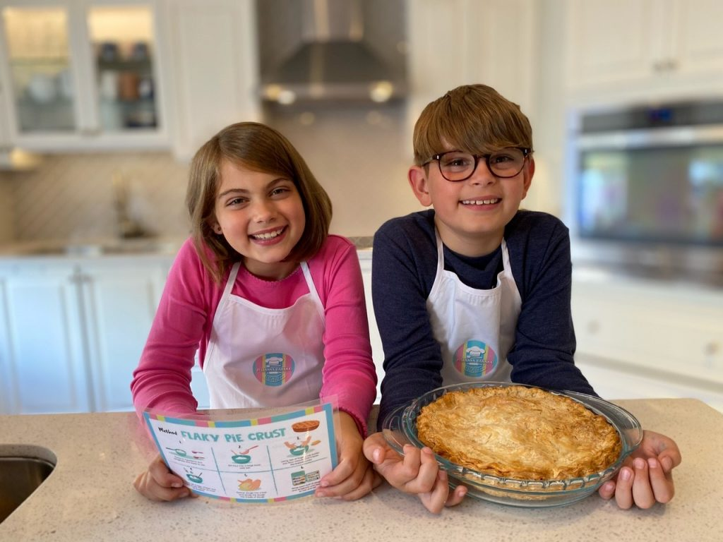 girl and boy at kitchen counter with recipe card and baked pie